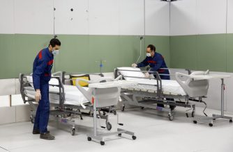 Iranian workers set up a makeshift hospital inside the Iran Mall, northwest of Tehran, on March 21, 2020 amid the coronavirus outbreak. - Iran said that 123 more people had died from coronavirus, raising the official death toll to 1,556 in the Islamic republic, one of the world's worst affected countries. (Photo by - / AFP)