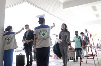 People have their temperatures checked amid concerns over the spread of the COVID-19 coronavirus at the immigration post in Myawaddy near the Thai border on March 23, 2020, as thousands of people crossed from Thailand as the border crossings were due to close because of the growing pandemic. - Tens of thousands of migrant labourers from Laos and Myanmar flooded bus stations and border crossings in Thailand on March 23, defying requests to stay put to prevent exporting infections of the deadly coronavirus. (Photo by STR / AFP)