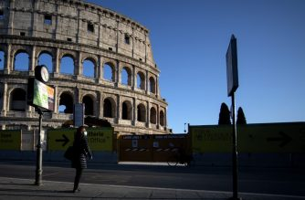 A woman wearing a protective mask waits at a bus stop near the Colosseum monument along a deserted Via dei Fori Imperiali on March 23, 2020 in Rome, during the country's lockdown aimed at stopping the spread of the COVID-19 (new coronavirus) pandemic. (Photo by Filippo MONTEFORTE / AFP)