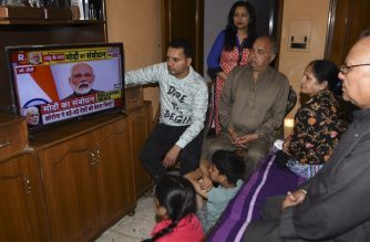 "A family watches Indian Prime Minister Narendra Modi's address to the nation on a television set on a television at their home in Amritsar on March 24, 2020. - India's 1.3 billion people will go under ""total lockdown"" from midnight on March 24 (1830 GMT) for 21 days to combat the spread of the coronavirus pandemic, Prime Minister Narendra Modi said. ""From 12 midnight today, the entire country will be in lockdown, total lockdown,"" Modi said in a national television address to the world's second most-populous nation. (Photo by NARINDER NANU / AFP)"
