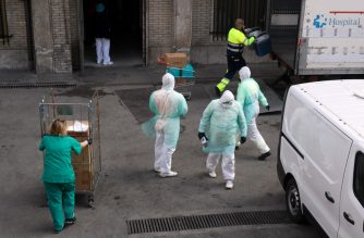 Health workers are pictured outside Gregorio Maranon hospital in Madrid on March 25, 2020. - Spain joined Italy today in seeing its death toll from the coronavirus epidemic surpass that of China, as more than a billion Indians joined a lockdown that has confined a third of humanity. (Photo by OSCAR DEL POZO / AFP)
