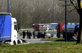Belgian police controls drivers' access authorizations between Belgium and France, on a resting area in Hensies, at the border near French city Valenciennes on March 26, 2020, after a strict lockdown came into effect to stop the spread of the COVID-19, the disease caused by the novel coronavirus. (Photo by FRANCOIS LO PRESTI / AFP)