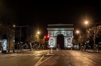 A picture shows the Arc de Triomphe in Paris, on March 26, 2020 on the evening of the tenth day of a strict lockdown in France aimed at curbing the spread of COVID-19, caused by the novel coronavirus. (Photo by Martin BUREAU / AFP)