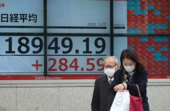 Pedestrians wearing face masks walk past a quotation board displaying the share price numbers on the Tokyo Stock Exchange in Tokyo on March 27, 2020. - Tokyo stocks opened more than three percent higher on March 27, tracking rallies on Wall Street on a massive US economic relief package. (Photo by Kazuhiro NOGI / AFP)