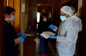 Sister Angel Bipendu (R), 46, a doctor part of the USCA special care unit of ATS Bergamo who performs home visits to patients infected or with symptoms of Covid-19, gives a prescription to a woman during a house visit to the woman's 80-year-old mother with potential symptoms of Covid-19, on March 27, 2020 near Bergamo, Lombardy, during the country's lockdown aimed at curbing the spread of the COVID-19 infection, caused by the novel coronavirus. (Photo by Piero CRUCIATTI / AFP)