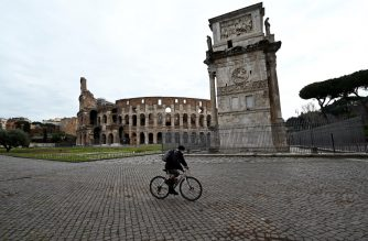A cyclist rides on the empty square in front of the Colisseum and the Arch of Constantine in Rome on March 28, 2020, during the country's lockdown aimed at stopping the spread of the COVID-19 (new coronavirus) pandemic. - Italy recorded a shocking spike in coronavirus deaths on March 27 with 969 new victims, the worst daily record for any country since the pandemic began. The infection rate however continued its downward trend, with the civil protection agency reporting nearly 86,500 confirmed cases in Italy. (Photo by Vincenzo PINTO / AFP)