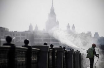 A municipal worker disinfects an embankment fence in Moscow on March 28, 2020 in front of the building of the Moscow State University, as the city attempts to curb the spread of the COVID-19, the disease caused by the novel coronavirus. (Photo by Alexander NEMENOV / AFP)