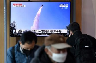 People watch a news broadcast showing file footage of a North Korean missile test, at a railway station in Seoul on March 29, 2020. - North Korea fired what appeared to be two short-range ballistic missiles off its east coast on March 29, the fourth such launch this month as the world battles the coronavirus pandemic. (Photo by Jung Yeon-je / AFP)