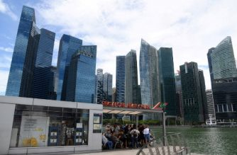 This photograph taken on February 18, 2020 shows visitors waiting for a boat tour along the Singapore river in Singapore, as the city's financial district is seen in the background. - Singapore's central bank eased monetary policy on March 30 as the city-state, seen as a bellwether for the health of global trade, heads for a deep recession due to the coronavirus pandemic. (Photo by Roslan RAHMAN / AFP)