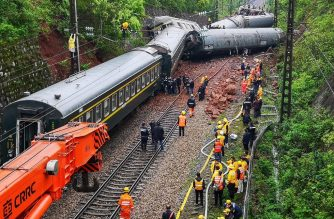 Rescuers search at the site where a train derailed in Chenzhou in China's central Hunan province on March 30, 2020. - A passenger train derailed after striking debris from a landslide in central China on March 30, injuring a number of passengers and staff, officials said. (Photo by STR / AFP) / China OUT