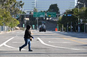 FILES: A woman wears a mask as she crosses an empty street near the Los Angeles Convention Center in downtown Los Angeles California March 30, 2020. - The California National Guard is currently setting up the convention center as a field hospital to help lessen the strain on LA-area hospitals during the coronavirus crisis. (Photo by Robyn Beck / AFP)