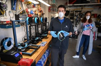 Jeremy Reitman oversees the production of medical quality PPE face shields for doctors and nurses on 3D printers (L) in the garage of his home as his wife Taryn Reitman (R) opens a box of the filament plastic used to make the masks, in the Calabasas neighborhood of Los Angeles, CA, March 30, 2020. - From amateur seamstresses and sewing clubs to Hollywood costume-makers, a patchwork army of volunteers across the United States is churning out gowns and masks for emergency workers battling coronavirus. The pandemic that has killed 2,500 nationwide has left medics dangerously exposed to the virus, with doctors forced to reuse scarce masks through the day as hospital supplies of personal protective equipment (PPE) rapidly dwindle. (Photo by Robyn Beck / AFP)