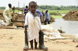 A boy carries father's footware salvaged from home submerged by flood at Wawa along Lagos - Ibadan expressway, Ogun State in southwest Nigeria, on October 5, 2016. - Thousands of Wawa community in Ogun State, southwest Nigeria have been rendered homeless as some of  their homes either has been submerged or washed away  and valuables lost to flood following the overflowing of Ogun River. (Photo by PIUS UTOMI EKPEI / AFP)