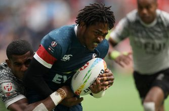 VANCOUVER, BRITISH COLUMBIA - MARCH 08: Kevon Williams #6 of USA scores a try while dragging Apenisa Cakaubalavu #5 of Fiji during their rugby sevens match at BC Place on March 08, 2020 in Vancouver, Canada.   Trevor Hagan/Getty Images/AFP
