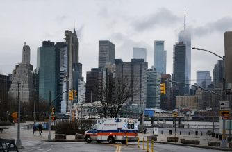 NEW YORK CITY, NY - MARCH 28: An ambulance pauses in Brooklyn while lower Manhattan looms in the background on March 28, 2020 in New York City, NY. Across the country schools, businesses and places of work have either been shut down or are restricting hours of operation as health officials try to slow the spread of COVID-19.   Spencer Platt/Getty Images/AFP