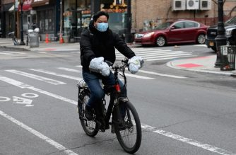 A food delivery man rides his bike on March 20, 2020 in the Brooklyn borough of New York. - New York Governor Andrew Cuomo on Friday ordered non-essential businesses to close and banned all gatherings, in an escalation of attempts to contain the deadly coronavirus pandemic. (Photo by Angela Weiss / AFP)