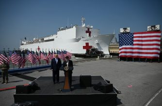 US Defense Secretary Mark Esper speaks as US President Donald Trump listens during the departure ceremony for the hospital ship USNS Comfort at Naval Base Norfolk on March 28, 2020, in Norfolk, Virginia. - The Comfort sails to New York City to aid in the coronavirus outbreak. (Photo by JIM WATSON / AFP)