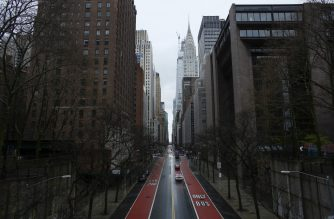 Cars cross 42th street as rain falls on March 28, 2020 in New York City. - US President Donald Trump said on March 28, 2020 that he's considering a short-term quarantine of New York state, New Jersey, and parts of Connecticut. (Photo by Kena Betancur / AFP)
