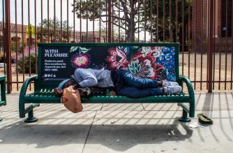 A  homeless man sleeps in a bench in Venice Beach, California on March 28, 2020. (Photo by Apu GOMES / AFP)
