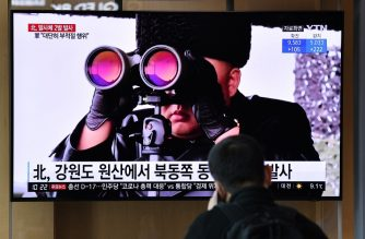 A man watches a news broadcast showing file footage of North Korean leader Kim Jong Un, at a railway station in Seoul on March 29, 2020. - North Korea fired what appeared to be two short-range ballistic missiles off its east coast on March 29, the fourth such launch this month as the world battles the coronavirus pandemic. (Photo by Jung Yeon-je / AFP)