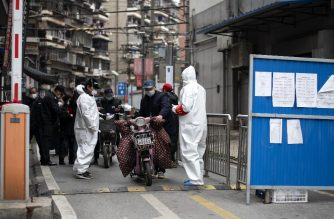 Community volunteers wearing protective gear (in white) check residents entering and leaving a compound in Wuhan in China's central Hubei province on March 31, 2020. - Wuhan, the central Chinese city where the COVID-19 coronavirus first emerged last year, partly reopened on March 28 after more than two months of near total isolation for its population of 11 million. (Photo by NOEL CELIS / AFP)