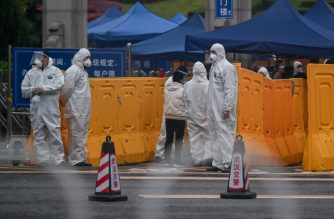 People wearing protective suits as a preventive measure against the COVID-19 coronavirus control an access point to the Biandanshan cemetery in Wuhan in China's central Hubei province on March 31, 2020. - As China's coronavirus epicentre of Wuhan awakens from its long nightmare, formerly locked-down citizens are beginning to re-emerge, but for many their first outdoor act in more than two months is grim: burying loved ones. (Photo by Hector RETAMAL / AFP)