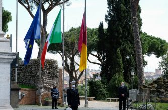 Municipal police officers stand at attention beside flags of Europe, Italy and Rome (From L) flying at half-mast during a minute of silence outside Rome's city hall at Capitoline Hill (Campidoglio), on March 31, 2020 as flags are being flown at half-mast in cities across Italy to commemorate the victims of the virus, during the country's lockdown aimed at curbing the spread of the COVID-19 infection, caused by the novel coronavirus. (Photo by ANDREAS SOLARO / AFP)