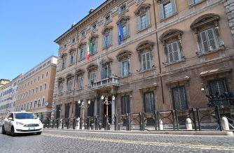 FILES: The Italian flag and the flag of Europe fly at half-mast on Palazzo Madama Senate building in Rome on March 31, 2020 as flags are being flown at half-mast in cities across Italy to commemorate the victims of the virus, during the country's lockdown aimed at curbing the spread of the COVID-19 infection, caused by the novel coronavirus. (Photo by ANDREAS SOLARO / AFP)