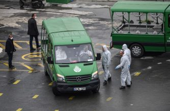 Officials wearing facemasks and personal protective equipment (PPE), as part of the measures adopted to fight against the spread of COVID-19, stand by a funeral vehicle leaving an Istanbul morgue, on March 31, 2020. - Turkey has so far officially recorded 10,827 cases of the novel coronavirus while 168 people have died. (Photo by Ozan KOSE / AFP)