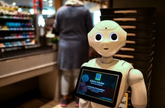 """Humanoid robot """"Prepper"""" stands on April 2, 2020 at the cash desk of a supermarket of the Edeka retail chain in Lindlar, western Germany, to explain protective measures and to promote solidarity with each other, amid the novel coronavirus / COVID-19 pandemic. (Photo by Ina FASSBENDER / AFP)"""