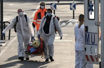French firefighters carry their tools and gears as they prepare to transfer patients contaminated by the COVID-19, the novel coronavirus, to other hospitals in France, at Paris Orly Airport, transformed into an emergency evacuation air base, on April 2, 2020. (Photo by Philippe LOPEZ / AFP)