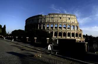 A woman walks with her dog by the Colosseum on April 2, 2020 in Rome, during the country's lockdown aimed at curbing the spread of the COVID-19 infection, caused by the novel coronavirus. (Photo by Filippo MONTEFORTE / AFP)