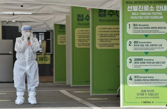 A Seoul city official wearing protective clothing waits to guide visitors for the COVID-19 coronavirus test at a walk-thru testing station set up at Jamsil Sports Complex in Seoul on April 3, 2020. - The number of officially reported coronavirus cases worldwide topped the one million mark on April 2, signifying a sharp acceleration in the number of infections and deaths over the past few weeks as the COVID-19 pandemic spreads exponentially. (Photo by Jung Yeon-je / AFP)