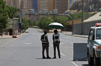 Police officers man a checkpoint in a street in Saudi Arabia's holy city of Mecca on April 3, 2020. - Saudi Arabia on April 2 extended curfew restrictions on Islam's two holiest cities to 24 hours to stem the spread of coronavirus as the number of deaths from the disease rose to 21. (Photo by - / AFP)