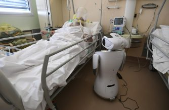 One of the six robots of the Circolo di Varese hospital stands near a patient, on April 3, 2020, to help the healthcare staff of the High Intensity Medicine department to assist twelve patients suffuring from the epedemic Covid-19, caused by the novel coronavirus. (Photo by Miguel MEDINA / AFP)