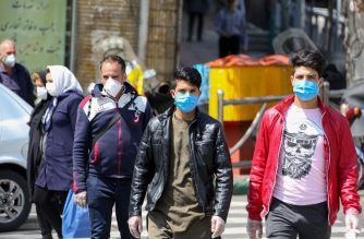 Iranians wear protective face masks against the novel coronavirus as they walk on a street in the capital Tehran on April 5, 2020. - The spread of the virus in Iran has slowed for the fifth day in a row, according to official figures released today by the authorities, who also announced plans for a gradual resumption of certain economic activities starting on April 11. (Photo by ATTA KENARE / AFP)
