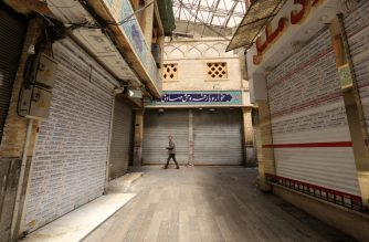 A lone Iranian man walks along an alley of a closed indoors market in the capital Tehran, during the novel coronavirus pandemic crisis, on April 5, 2020. - The spread of the virus in Iran has slowed for the fifth day in a row, according to official figures released today by the authorities, who also announced plans for a gradual resumption of certain economic activities starting on April 11. (Photo by ATTA KENARE / AFP)