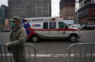 An ambulance drives by a US Army National Guards member standing outside of the Jacob K. Javits Center on April 5, 2020 in New York. - The coronavirus death toll in New York state spiked to 4,159, the governor said, up from 3,565 a day prior. The toll increase of 594 showed a slight decrease in the day-to-day number of lives lost compared to the previous day.  Governor Andrew Cuomo told journalists it was too soon to tell whether the decrease from the previous record of 630 deaths in one day was statisically significant. (Photo by Bryan R. Smith / AFP)
