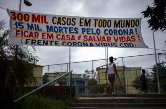 "A banner reading ""300,000 cases in the world, 15,000 deaths because of coronavirus! Stay at home and save lives!"" hangs at the Cidade de Deus (City of God) favela in Rio de Janeiro, Brazil on April 7, 2020, during the novel coronavirus (COVID-19) outbreak. (Photo by MAURO PIMENTEL / AFP)"