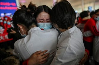 A medical staff member from Jilin Province (C) cries while hugging nurses from Wuhan after working together during the COVID-19 coronavirus outbreak in Wuhan during a ceremony at the Tianhe Airport after it was reopened today, in Wuhan in China's central Hubei province on April 8, 2020. - Thousands of Chinese travellers rushed to leave COVID-19 coronavirus-ravaged Wuhan on April 8 as authorities lifted a more than two-month prohibition on outbound travel from the city where the global pandemic first emerged. (Photo by Hector RETAMAL / AFP)