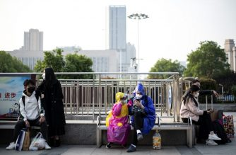 People wearing face masks sit outside Hankou Railway Station in Wuhan as people arrive in the hope of taking one of the first trains leaving the city in China's central Hubei province early on April 8, 2020. - Thousands of relieved citizens streamed out of China's Wuhan on April 8 after authorities lifted months of lockdown at the coronavirus epicentre, offering some hope to the world despite record deaths in Europe and the United States. (Photo by NOEL CELIS / AFP)