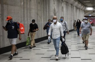 Commuters wear face masks in a subway station in Santiago as a precautionary measure against the spread of the new coronavirus, COVID-19, on April 8, 2020. - The Chilean government decreed on Monday the mandatory use of face masks on all public transport, following the new recommendations of the World Health Organization (WHO). (Photo by Martin BERNETTI / AFP)