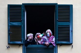 People with protective masks look from their windows at artists performing in the courtyard of a popular apartment building for the show Sotto lo Stesso Cielo tour (Under the Same Sky tour) in San Basilio suburbs of Rome on April 18, 2020, during the country's lockdown aimed at stopping the spread of the COVID-19 (new coronavirus) pandemic. (Photo by Alberto PIZZOLI / AFP)