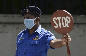 Sri Lankan Navy personnel wearing a facemask holds a stop sign at a checkpoint during a government-imposed nationwide lockdown as a preventive measure against the COVID-19 coronavirus, in Colombo on April 26, 2020. - Sri Lanka has reversed plans to end its virus lockdown on Aril 27, extending it for another week after a spike in coronavirus infections including at a naval base. (Photo by LAKRUWAN WANNIARACHCHI / AFP)