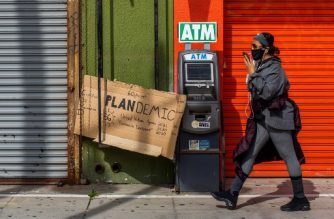 "A woman wearing a mask, walks by the closed stores of the Boardwalk in Venice, California on April 26, 2020. - Los Angeles County beaches are still off limits under the county's ""Safer at Home"" order scheduled to be enforced through at least May 15 amid the novel coronavirus pandemic. (Photo by Apu GOMES / AFP)"