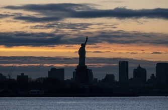 The sun rises behind the Statue of Liberty in New York City   on April 28, 2020 as seen from New Jersey. (Photo by Johannes EISELE / AFP)