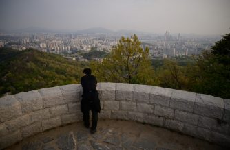 A man looks out from a viewpoint overlooking the city skyline of Seoul on April 30, 2020. - South Korea on April 30 reported no new locally transmitted coronavirus cases for the first time since the disease was detected in the country more than two months ago. (Photo by Ed JONES / AFP)
