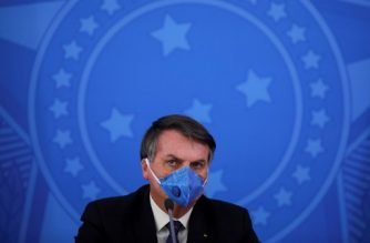 Brazil's President Jair Bolsonaro wears a face mask during a press conference on the coronavirus pandemic COVID-19 at the Planalto Palace in Brasilia, Brazil on March 20, 2020. - Brazil's government on Friday drastically downgraded its growth projections for 2020 by 2.1 percent to practically zero (0.02 percent) due to the coronavirus pandemic. (Photo by Sergio LIMA / AFP)