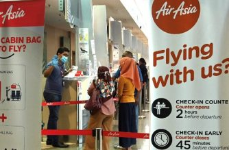 Passengers speak to a worker wearing a protective face mask and gloves as they check in for a flight at Penang International Airport as AirAsia resumed domestic flights in Malaysia, in Penang on April 29, 2020, after the airline's operations were curtailed due to the spread of the COVID-19 coronavirus. (Photo by GOH CHAI HIN / AFP)