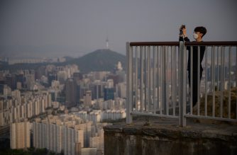 A man wearing a face mask takes photos at a viewpoint overlooking the city skyline of Seoul on April 30, 2020. - South Korea on April 30 reported no new locally transmitted coronavirus cases for the first time since the disease was detected in the country more than two months ago. (Photo by Ed JONES / AFP)